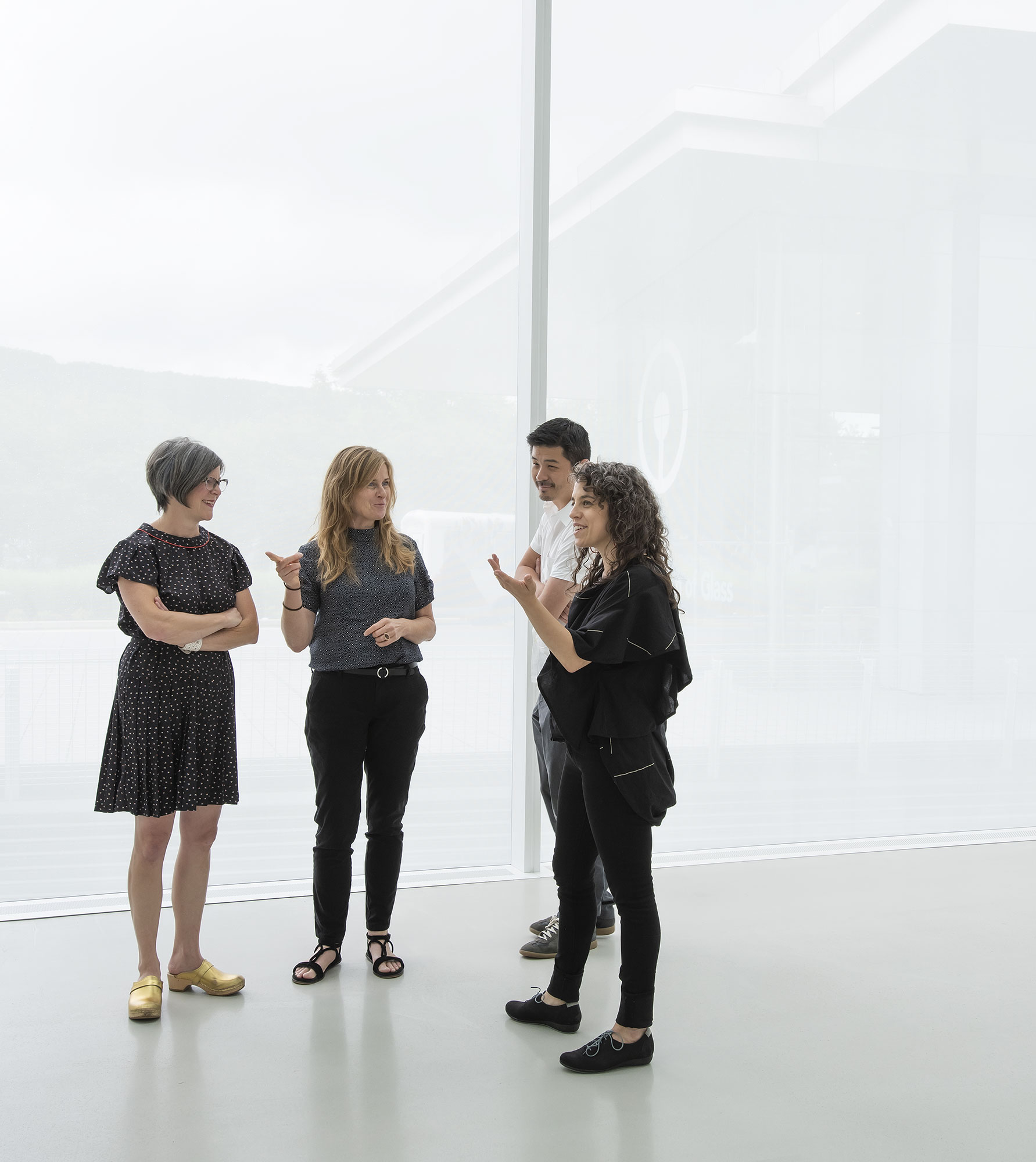 Photo of 3 women and one man standing and talking in brightly lit space