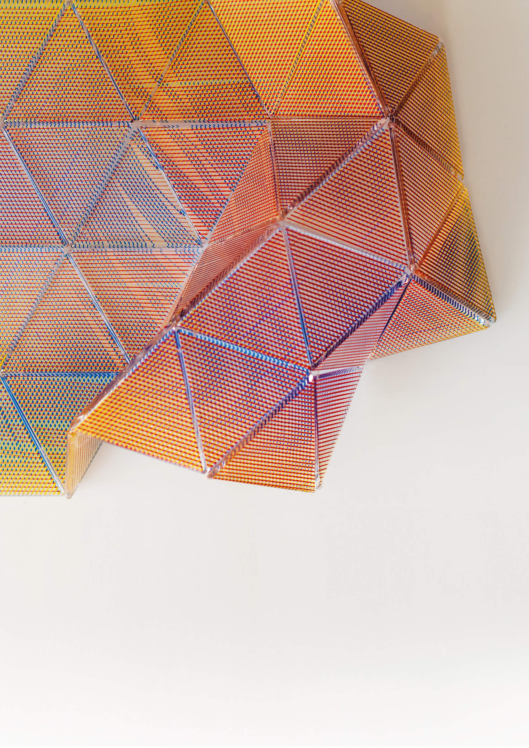 Photo of amber-colored glass triangled in articulated folding sheet
