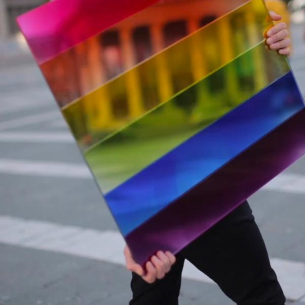 A person carries a large, square mirror with six colored horizontal stripes—each a color of the rainbow—through a crosswalk. The mirror reflects the façade of a neo-classical building.