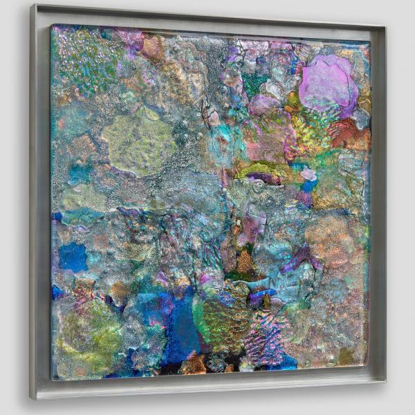 Square of multi-colored irridescent glass with ripples and bubbles in a thin square aluminum frame hanging on a white wall.