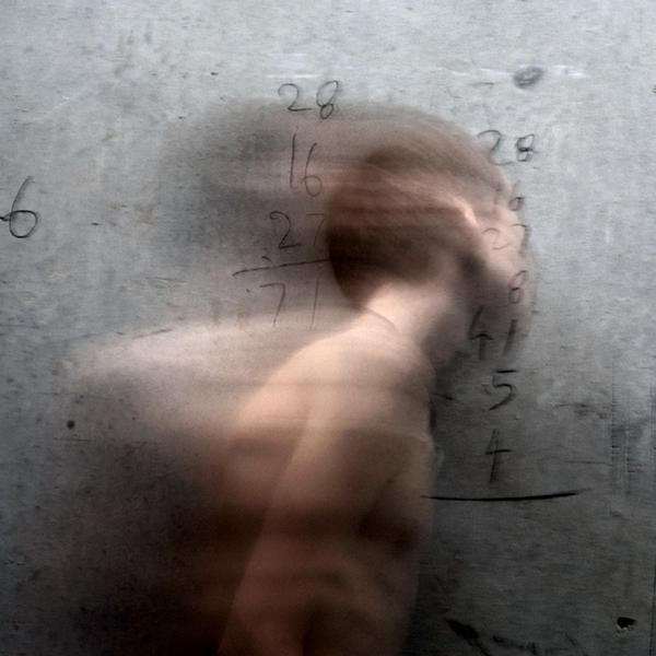 Rectangular panel of glass on raw steel that shows a light-skinned man in blurred movement from the side. There is a series of numbers etched into the surface.