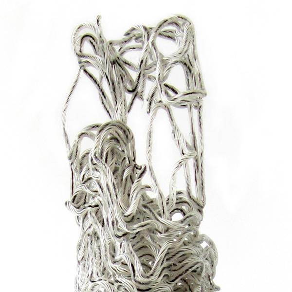 Shoelace-thin glass cane with clear, white, and black lines drizzled into a standing tall vertical sculpture that is more dense in the bottom third and has more openwork at the top.