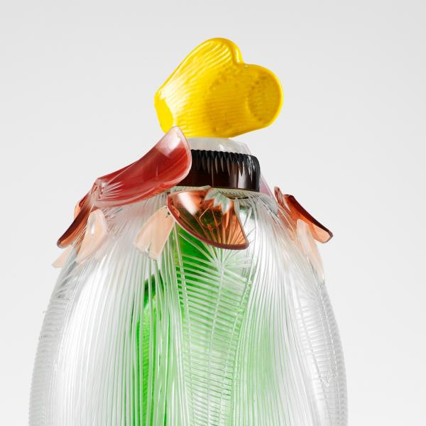 A clear glass dome with cut vertical stripes sits atop a square green glass bottle, with red, orange and black broken cut glass shards up near the neck topped by a small piece of yellow glass shaped like a mitten.