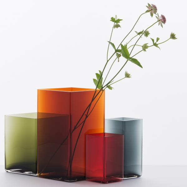 Four square glass vases of different heights and colors—green, orange, red, blue. Two stems of purple flowers lean in the orange vase.