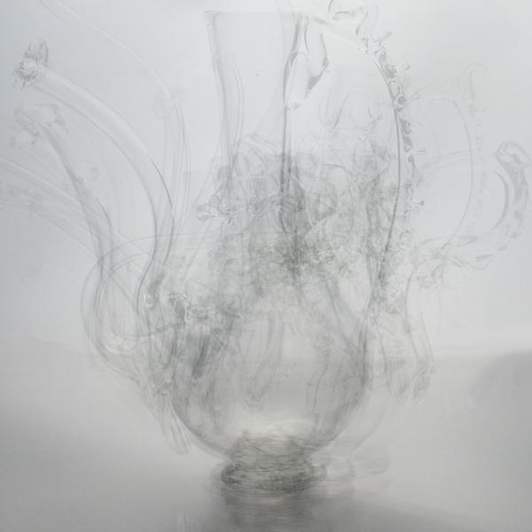 Photograph of superimposed clear glass pitchers and vases faded to look almost ghost-like.