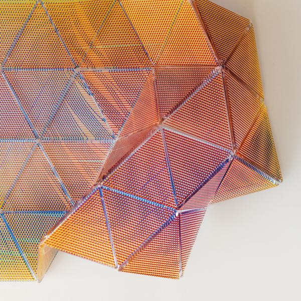Triangular glass panels are hinged to create a flexible surface. The panels are screen-printed with digitally-generated filigree patterns in oranges, reds, golds, and yellows.