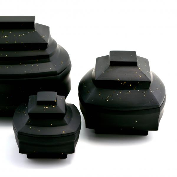 Three rounded square-shaped black glass jars with gold flecks. Each jar is a different size; the lids dome up into smaller squares.