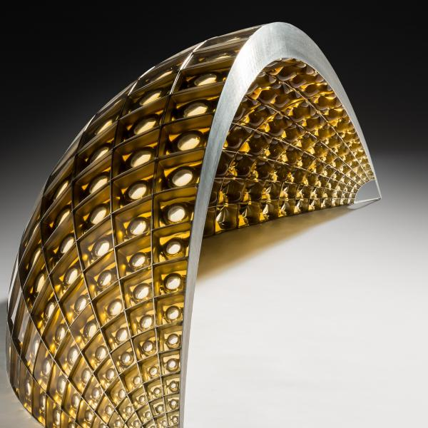 "A curved wedge of glass perforated with cellular glass ""lenses,"" held together with a steel armature. Colors range from gold on the narrow ends to bronze in the wide center."