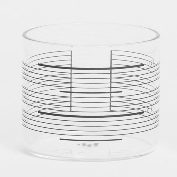Set of four short clear drinking glasses decorated with black measuring stripes that resemble those that might be found on laboratory glassware.