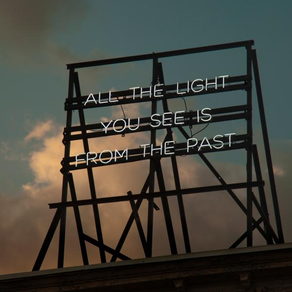 "Scaffolding on top of a building supports neon letters that say, ""All the light you see is from the past."""