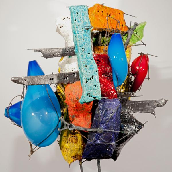 A mixed-media sculpture with blue blown glass vessels and glazed ceramic in orange, red, purple, silver, yellow, lime, and light blue. The pieces are held together with metal wire and the work sits atop a small industrial metal pedestal.