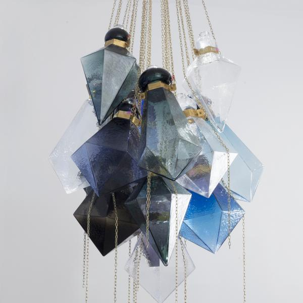 Oversized glass prisms in blue, white, gray, and black hang from gold chains to form a chandelier of crystal shapes.