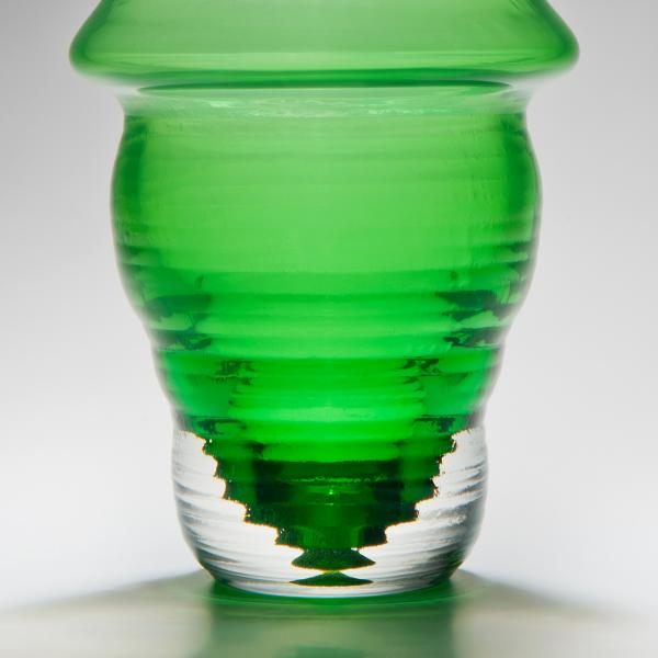 Green vase shaped similar to neoclassical style balusters. The top of the vase is very light green and changes to a very dark green at the bottom.