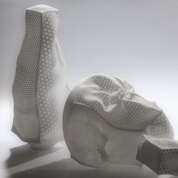 Three white blown glass sculptures made to look like slightly crumpled mesh fabric pillows. Two are narrow rectangles and the one in the middle is looks more like an inflated cube.