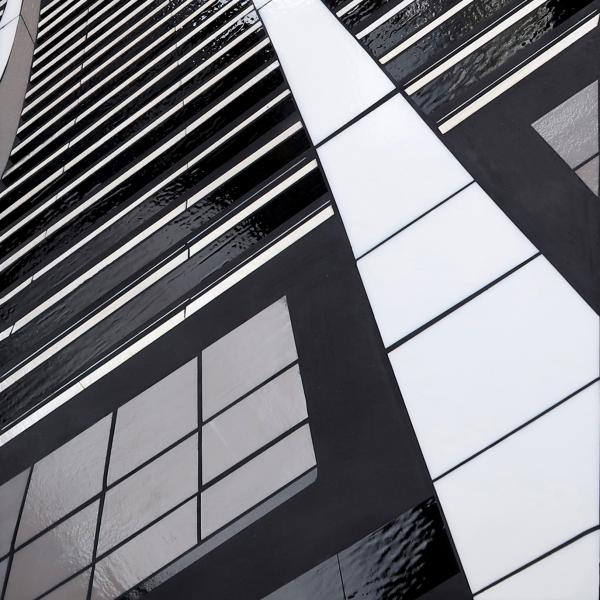 Glass panel assembled to look as if the viewer were looking up the façade of a tall skyskraper. Glass is in varying shade of white and black held together with grout.