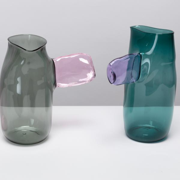 Three slightly misshapen glass jugs, each with a paddle-like handle on the side. The first jug is pink with a green handle; the second gray with a pink handle; the third is teal with a purple handle.