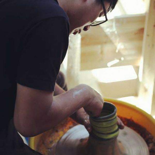 A man wearing glasses is hunched over a pottery wheel forming a vessel with yellow stripes.