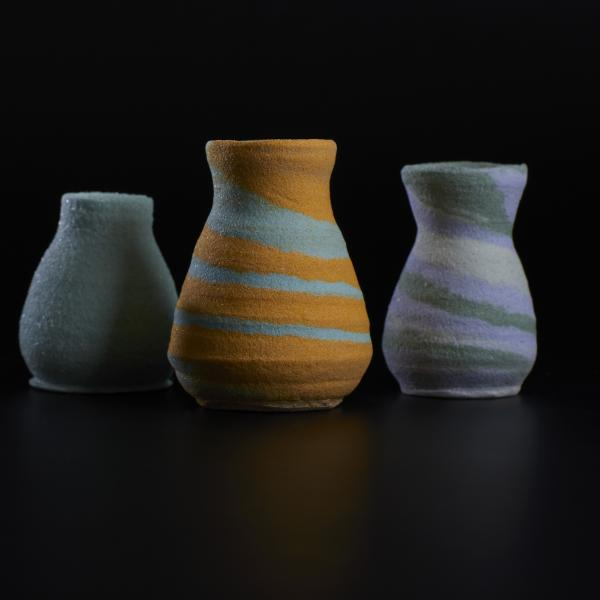 Five small, colorful vases look as if they have a sandy texture. L-R, they are tan and brown, lavender and gray, light green, orange and light green, and lavender, gray and cream.