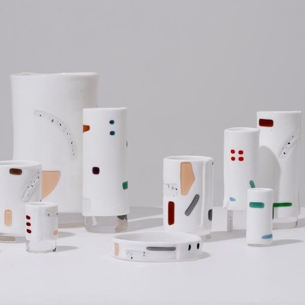 Fifteen vessels of varying sizes sit on a table. The vessels are mostly white, but each has swatches of color—red, green, purple, peach—on its exterior.