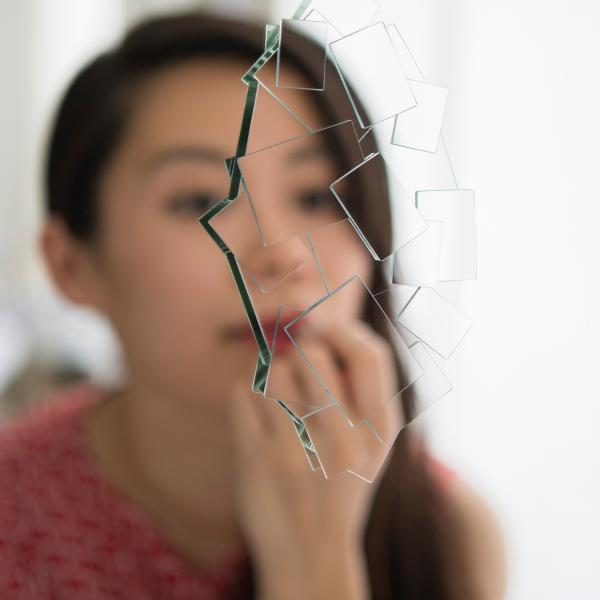Fragments of mirrored glass are attached to a mirror breaking up the reflection of the Asian woman looking into the mirror to apply lipstick.