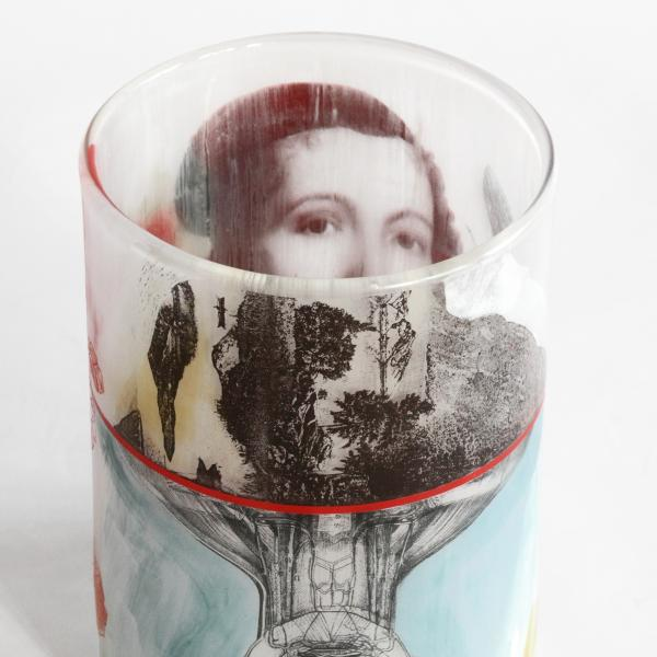 A blown glass cup decorated with colorful decals including the top half of a woman's face, a black and white landscape scene, and an upsidedown anatomical sketch of a head and upper torso on a blue background.
