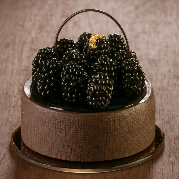 Rendered in glass, a round chocolate cake is covered blackberries, the center berry has a decorative gold flourish. The cake sits on a round gold plate.
