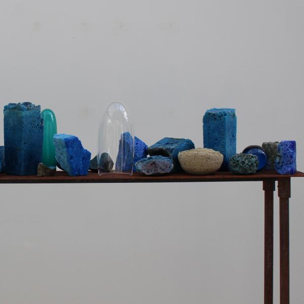 24 pieces of unfinished glass in blue hues sit on a long, narrow brown table. Some of the glass is tall and square, others short and round, each a unique shape and texture.