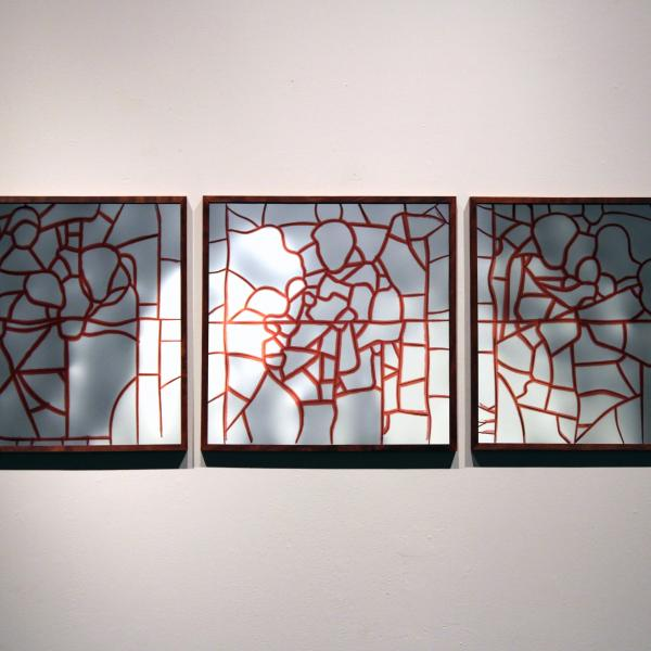 Three square panels, in the style of stained glass, in wood frames depict stylized figures in mirrored glass pieces outlined in red.