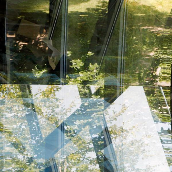 A slightly curved panel of glass, about 5 feet tall, shows reflections of windows, trees, a desk with a computer on it, and sky.