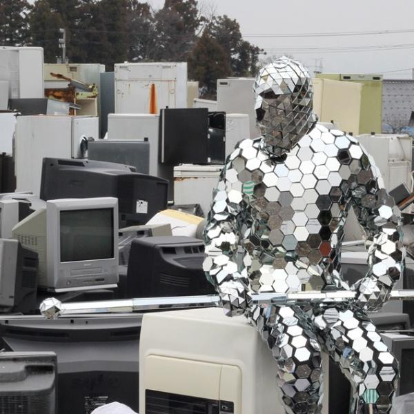 A man wearing an outfit covered in mirrored hexagons and holding a mirrored staff sits on an air conditioner in a junkyard filled with TVs, computer monitors, refrigerators, and other electronic detritus.