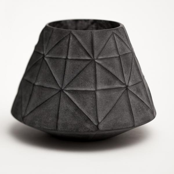 A black vessel shaped like a cone without a top is covered in raised black lines—horizontal, vertical, and diagonal—that breaks the surface into triangle shapes.
