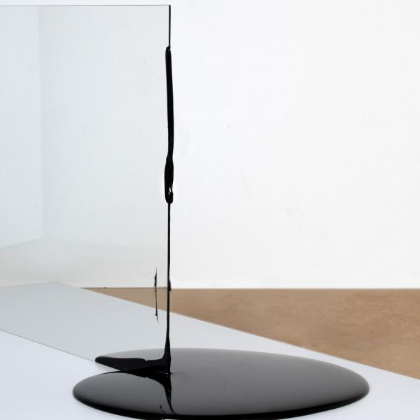 A sheet of clear glass sits upright on a white platform. The top edge of the glass has drips of asphalt on it. The bottom edge splits a shiny black puddle of asphalt.