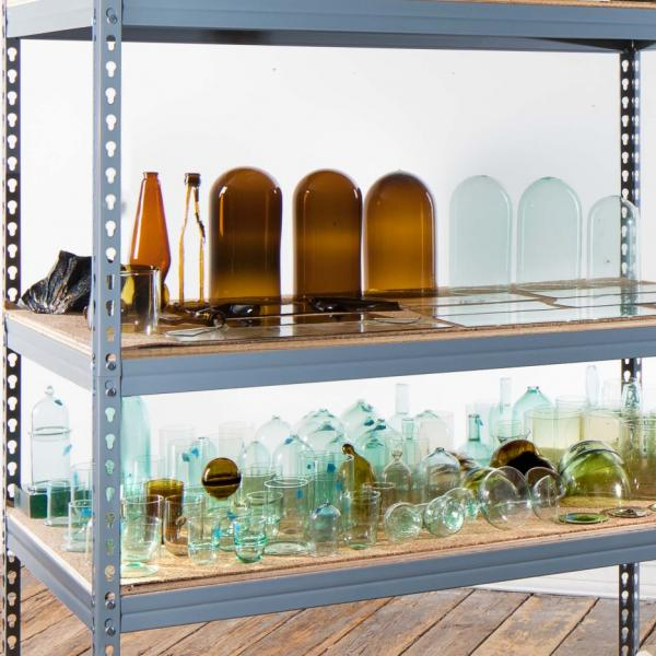 A five-tiered gray metal shelf holds some of the raw materials for glassmaking. From bottom to top: four large molds; a variety of green and clear recycled glass; amber and clear glass vessels and pieces of flat glass; four large oyster shells; eight tall, thin clear glass vessels and a mold. On the floor are three circular molds and a chunk of rock.