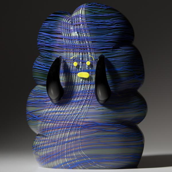 A chubby glass monster with blue and purple horizontal stripes that look like string wrapped around it. It has black arms, and a yellow mouth, eyes, and eyebrows.