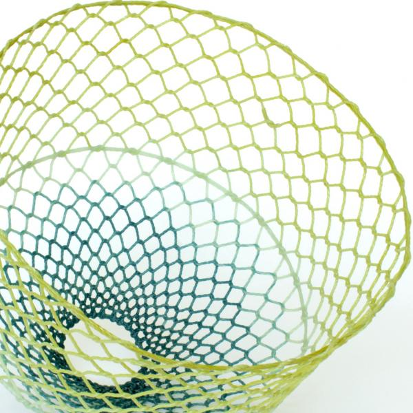 Yellow, blue, and green glass fiber ropes woven into a fishnet-like basket that is wide at the yellow end and narrow at the blue end.