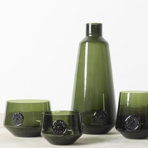 A dark green glass decanter and cups, two cups to the left and one cup to the right. Each vessel has a stamped seal on the front in the same dark green glass.