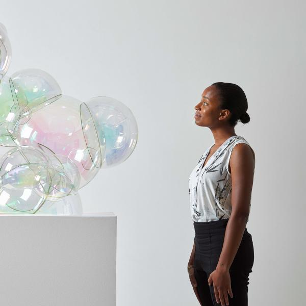 A dark-skinned woman stands next to a white pedestal looking at a clump of large iridescent glass bubbles that seem to be emerging from the top of the pedestal.