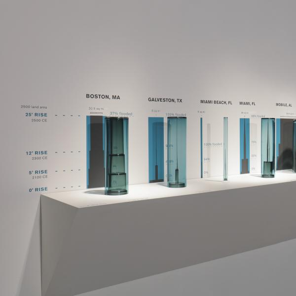 15 bluish glass cylinders on a white shelf, all the same height but different widths. Above each is the name of a city and state, and to the right are listed percentages. Inside each cylinder is a piece of glass the same width at the bottom, but that ends in a point at the top.