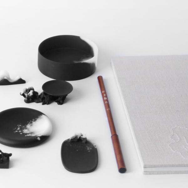Tools of Chinese calligraphy, viewed from above, are rendered in black glass with a matte finish with splotches of white along the tips and edges.