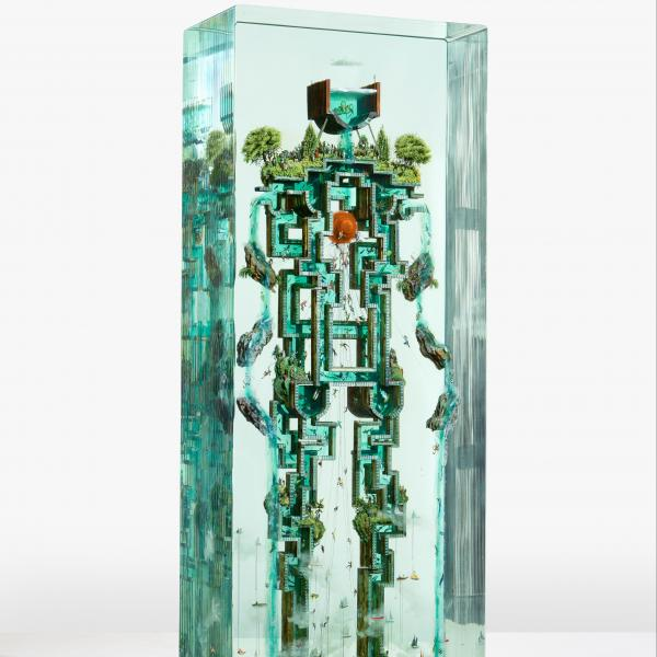 A robot encased in a block of clear glass is made from what looks like steel scaffolding and is covered in trees and plant matter. Water runs through its body around a red circular object in the center where a heart would be.