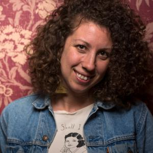 Woman with medium-length curly brown hair wearing a printed t-shirt and jean jacket stands in front of a floral wallpaper background.