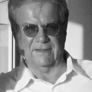 Black and white headshot of a middle-aged man with light colored hair wearing sunglasses and a white button-down shirt.