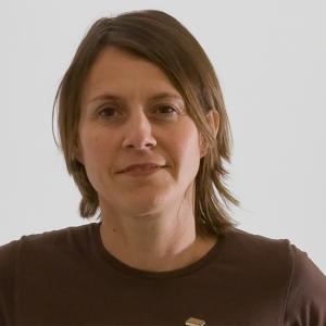 Woman with medium-length brown hair wearing a brown t-shirt.