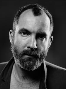 Black and white photo of a bearded man with a receding hairline.