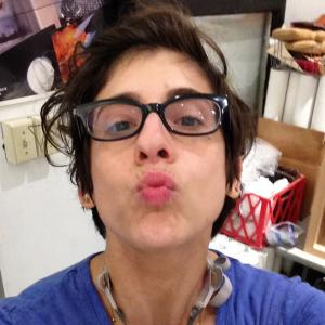 Woman with short brown hair wearing black glasses and a blue t-shirt making a kiss face at the camera. A respirator hangs around her neck.