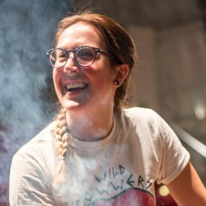 "Woman with long, braided, reddish hair, glasses, wearing a ""Wild Powwers"" band t-shirt. She cradles a hot glass piece on the end of a blowpipe in steaming newspaper."