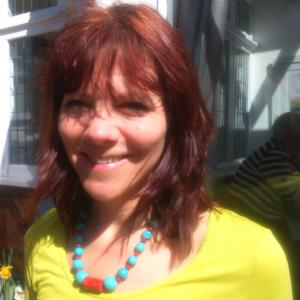 A smiling woman with medium-length red hair wearing a bright yellow shirt and red/turquoise necklace. A house and garden fill the background.
