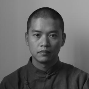 Black and white headshot of a man with dark hair shaved close to his head wearing a medium-colored changsan.
