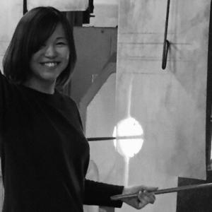 Black and white photograph of a smiling woman with medium-length dark hair. She stands in front of a glass furnace holding a blowpipe in her left hand. Her right hand is raised above her head.